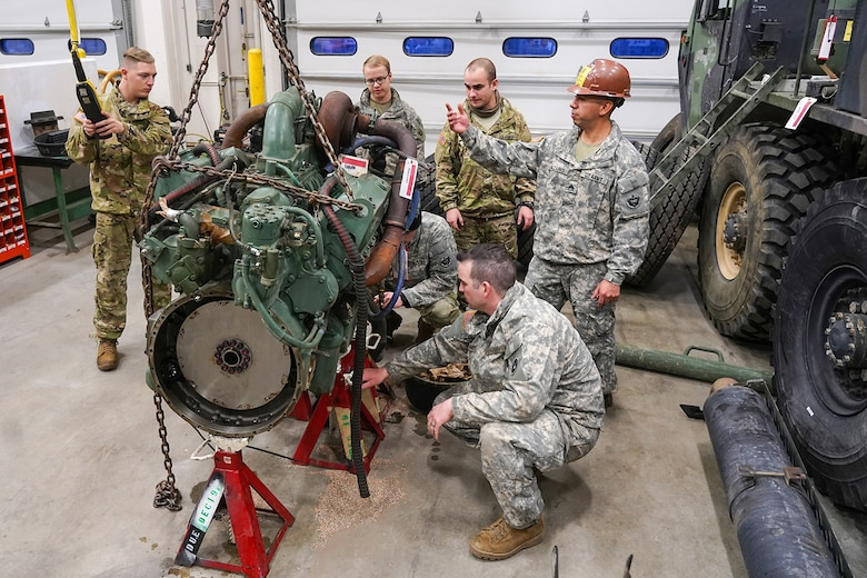 Army Staff Sgt. Federico Lazaro, a native of Chicago, right, assigned to the 109th Transportation Company, 17th Combat Sustainment Support Battalion, U.S. Army Alaska, supervises his Soldiers moving a damaged engine from an M984A2 Heavy Expanded Mobility Tactical Truck wrecker with a hoist in their motor pool on Joint Base Elmendorf-Richardson, Alaska, Dec. 13, 2019. The M984A2 is an eight-wheel drive, diesel-powered, variant of the HEMTT used in vehicle recovery operations.