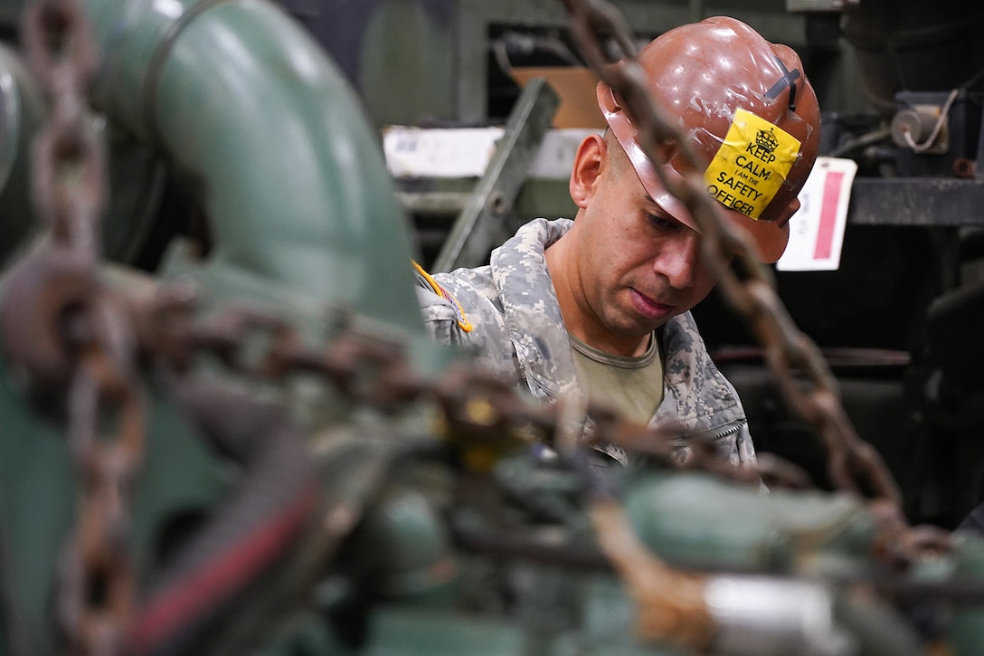 Army Staff Sgt. Federico Lazaro, a native of Chicago, assigned to the 109th Transportation Company, 17th Combat Sustainment Support Battalion, U.S. Army Alaska, supervises his Soldiers moving a damaged engine from an M984A2 Heavy Expanded Mobility Tactical Truck wrecker with a hoist in their motor pool on Joint Base Elmendorf-Richardson, Alaska, Dec. 13, 2019. The M984A2 is an eight-wheel drive, diesel-powered, variant of the HEMTT used in vehicle recovery operations.