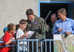 Maj. Ben Gilliland, Orange Flag Director, 411th Flight Test Squadron, assists a STARBASE Edwards student on providing coordinates to an airborne fighter pilot during an Orange Flag exercise at Edwards Air Force Base, California, Dec. 10. (Air Force photo by Giancarlo Casem)