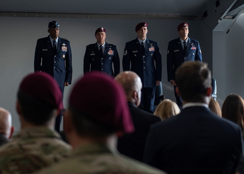 Four Airmen stand at attention in front of a crowd of people.
