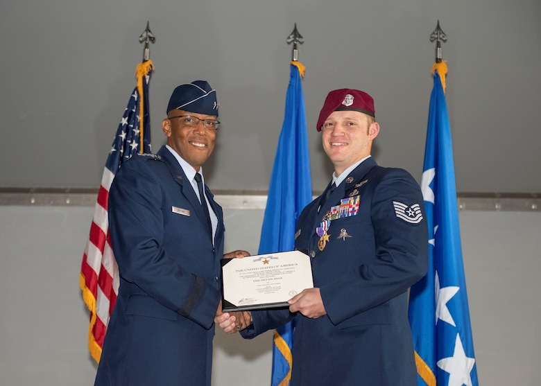 An Airman holds an award while presenting it to another Airman.