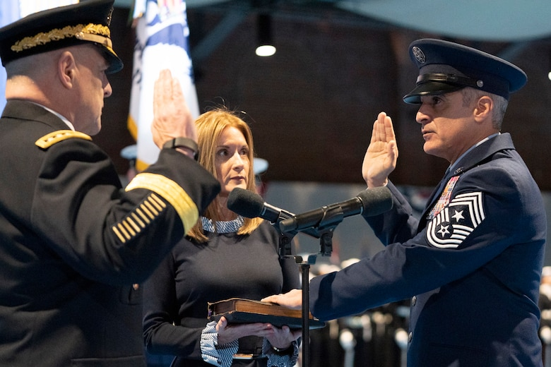 "Chairman of the Joint Chiefs of Staff Army Gen. Mark A. Milley and Senior Enlisted Advisor to the Chairman of the Joint Chiefs of Staff Ramon ""CZ"" Colon-Lopez face each other and raise their right hands."