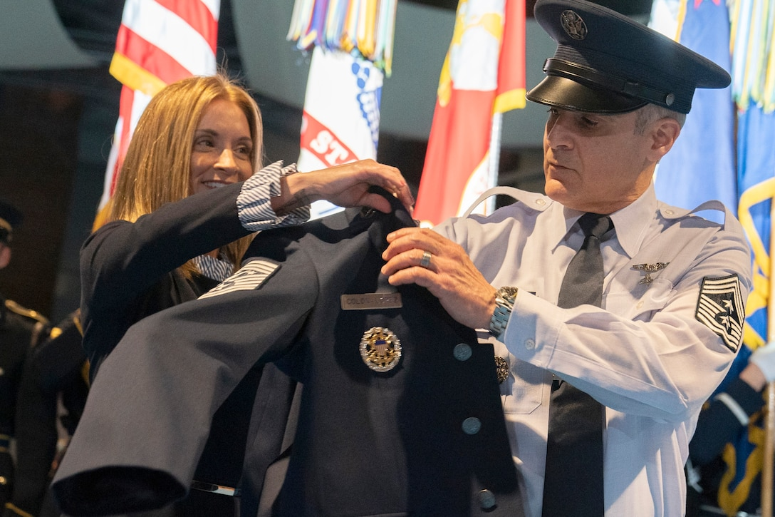"""The wife of Senior Enlisted Advisor to the Chairman of the Joint Chiefs of Staff Ramon """"CZ"""" Colon-Lopez hands him a jacket."""