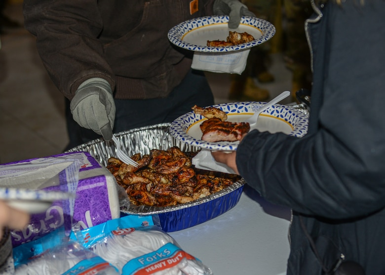 U.S. Air Force Airmen from the 31st Fighter Wing make a plate of ribs at Aviano Air Base, Italy, Dec. 13, 2019. Free BBQ, gelato, and hot chocolate were all provided at the grand opening ceremony for a new dorm pavilion. (U.S. Air Force photo by Airman Thomas S. Keisler IV)