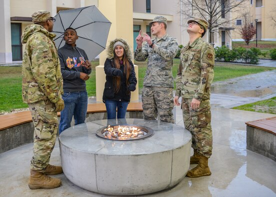 U.S. Air Force Airmen from the 31st Fighter Wing linger around a fire pit attached to a new dorm pavilion at Aviano Air Base, Italy, Dec. 13, 2019. The new pavilion will serve as a community focal point for Airmen to hang out and have a good time. (U.S. Air Force photo by Airman Thomas S. Keisler IV)
