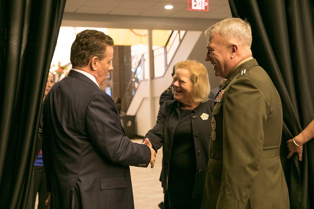U.S. Marine Corps Gen. Kenneth F. McKenzie Jr., right, the commander of U.S. Central Command, and his spouse Mrs. Marilyn P. McKenzie, center, meet James P. McVay, Chief Executive Officer of the Outback Bowl, at Raymond James Stadium in Tampa, Florida, Dec. 12, 2019. (U.S. Marine Corps photo by Sgt. Roderick Jacquote)
