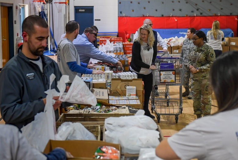 Event volunteers distribute groceries to participants during a holiday food distribution at Joint Base Langley-Eustis, Virginia, Dec. 11, 2019