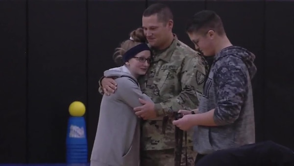Indiana National Guardsman embraces his family upon his arrival from an overseas deployment.