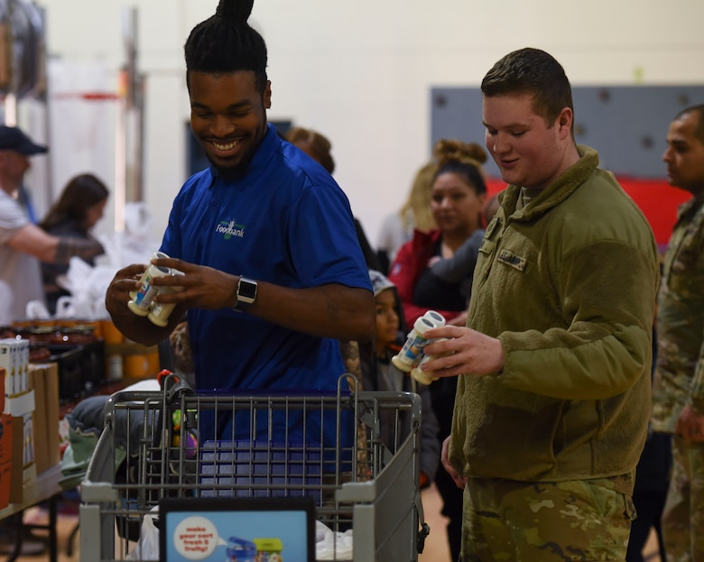 Andrew Council, Virginia Peninsula Foodbank product manager, and U.S. Army Pfc. Daniel Smith, 331st Transportation Company, 11th Battalion, 7th Transportation Brigade allied trade specialist, put groceries in a cart during a holiday food distribution at Joint Base Langley-Eustis, Virginia, Dec. 11, 2019.