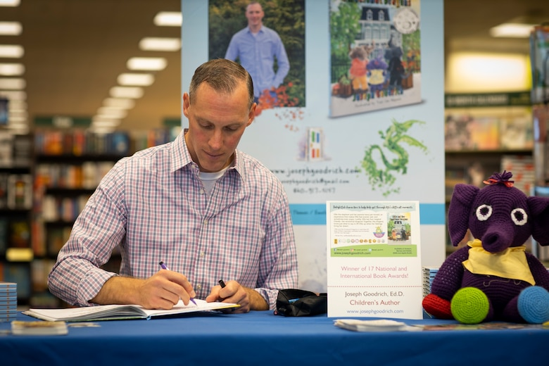 Marine Maj. Joseph Goodrich signs his book during his book-signing in Jacksonville, North Carolina, Nov. 30, 2019. Goodrich, now a published author, read his book to fans and signed copies of his book for young readers. Goodrich is the executive officer of Marine Aerial Refueler Transport Squadron 252. (U.S. Marine Corps photo by Cpl. Cody Rowe)