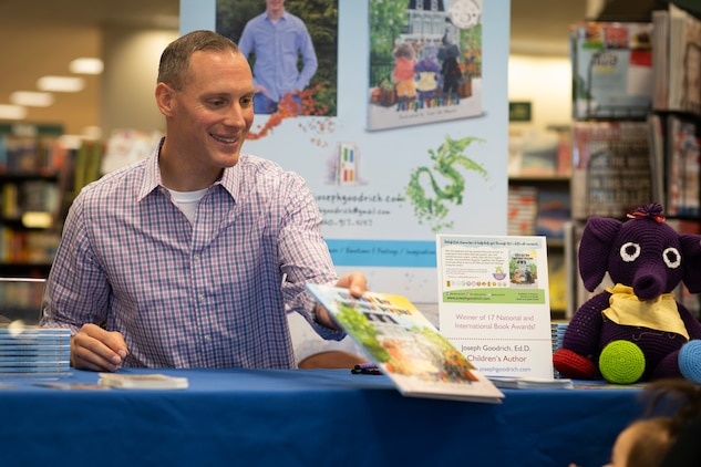 Marine Maj. Joseph Goodrich hands a children's book to a young reader at a book store in Jacksonville, North Carolina, Nov. 30, 2019. Goodrich, now a published author, read his book to fans and signed copies of his book for young readers. Goodrich is the executive officer of Marine Aerial Refueler Transport Squadron 252. (U.S. Marine Corps photo by Cpl. Cody Rowe)
