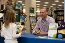 Marine Maj. Joseph Goodrich speaks to a young reader in Jacksonville, North Carolina, Nov. 30, 2019. Goodrich, now a published author, read his book to fans and signed copies of his book for young readers. Goodrich is the executive officer of Marine Aerial Refueler Transport Squadron 252. (U.S. Marine Corps photo by Cpl. Cody Rowe)