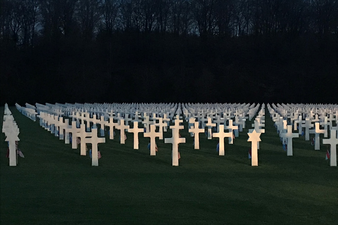 White crosses and Stars of David mark graves in a military cemetery.