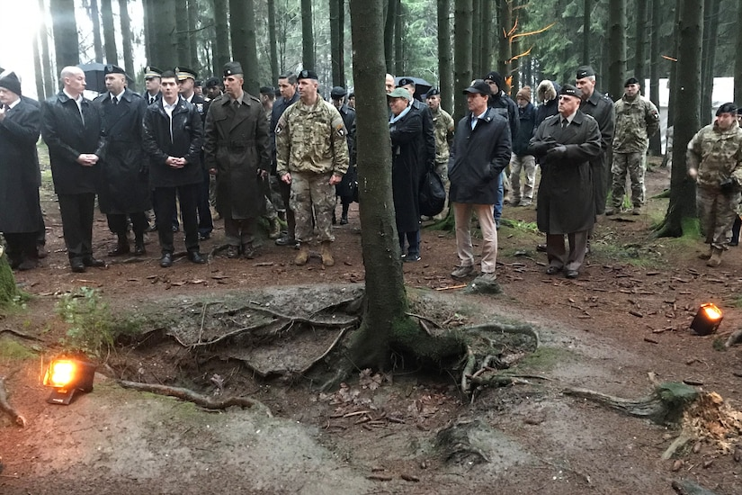 Civilians and military personnel view a World War II battle site.