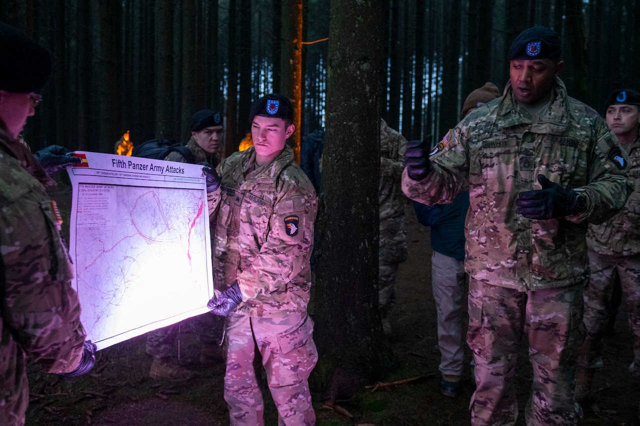 "Soldiers hold a briefing chart titled ""Fifth Panzer Army Attacks"" as another soldier briefs visitors at a World War II battle site."