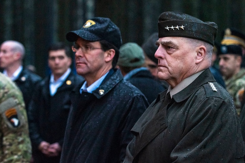 Defense secretary and Joint Chiefs chairman visit a site from World War II's Battle of the Bulge. Their hats are wet with rain.