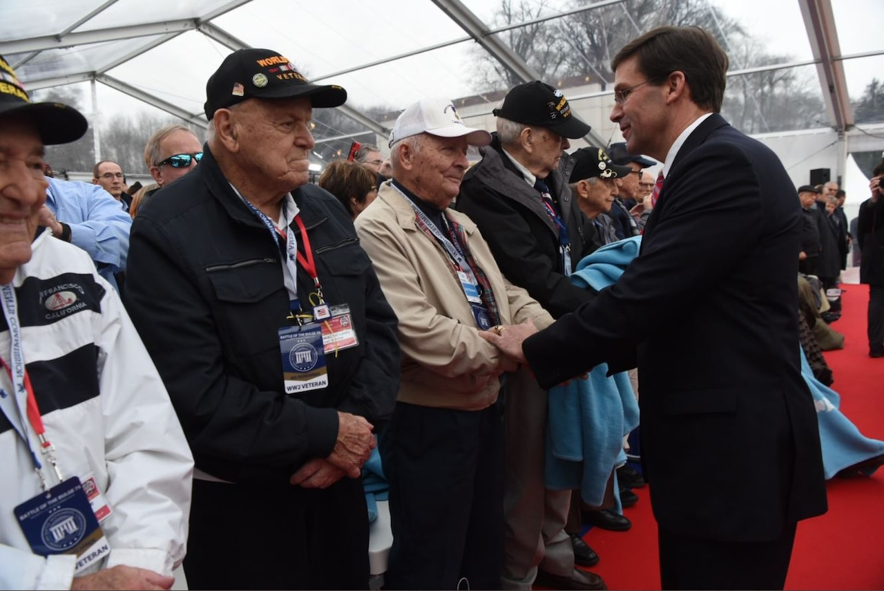 A man shakes hands with a line of WWII veterans.