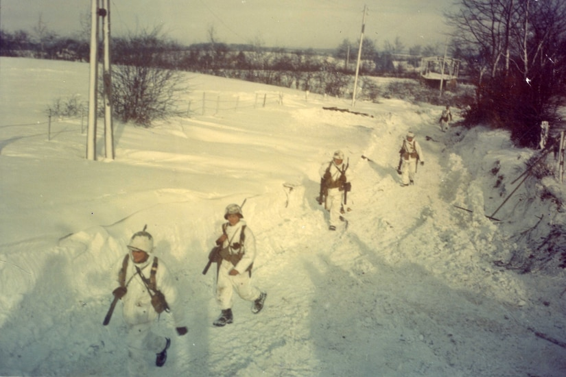 Soldiers walk through the snow.