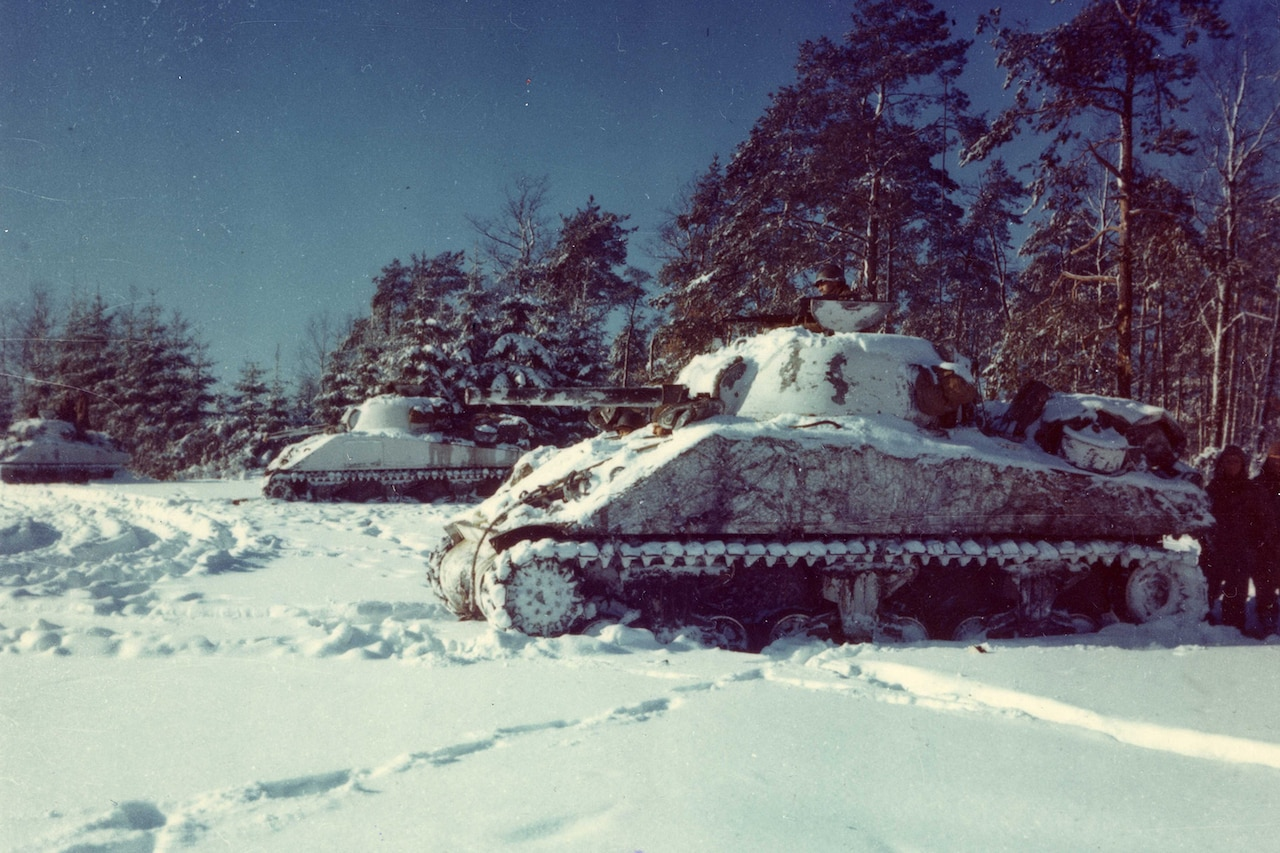 Several tanks sit in the snow in front of a line of trees.