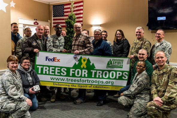 """Senior Airman Lamont Hicks, 910th Airlift Wing commander's support staff, stands with a group of 910th AW personnel and others after receiving the honorary """"First Tree of Christmas"""" in a ceremony held in the USO of Northern Ohio's on-base lounge here, Dec. 6, 2019."""