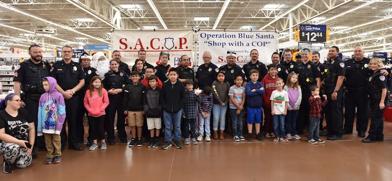 Participants and volunteers at the Operation Blue Santa Shop with a Cop event in San Angelo, Texas, stand for a group photo before beginning shopping Dec. 14, 2019. After shopping volunteers also wrapped any presents for the participants. (U.S. Air Force photo by Senior Airman Seraiah Wolf)