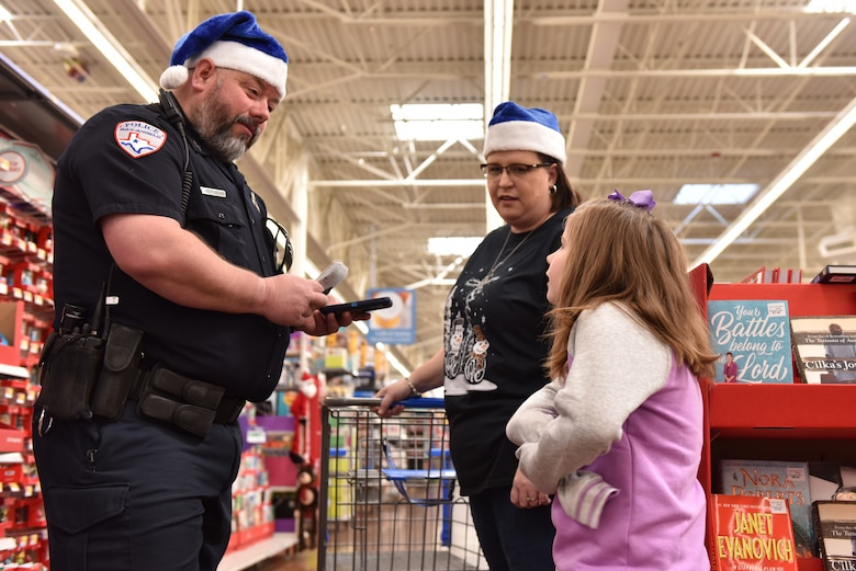 A San Angelo police officer talks with a child about their shopping list during the Operation Blue Santa Shop with a Cop event in San Angelo, Texas, Dec. 14, 2019. The children were able to pick out gifts for various family members and also themselves. (U.S. Air Force photo by Senior Airman Seraiah Wolf)