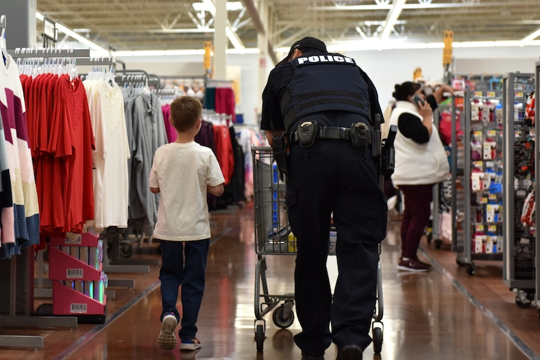 A child and his San Angelo police officer shopping partner walk while discussing what else they need to buy during the Operation Blue Santa Shop with a Cop event in San Angelo, Texas, Dec. 14, 2019. Each child who signed up for the event shopped with a police officer to purchase gifts for their family. (U.S. Air Force photo by Senior Airman Seraiah Wolf)