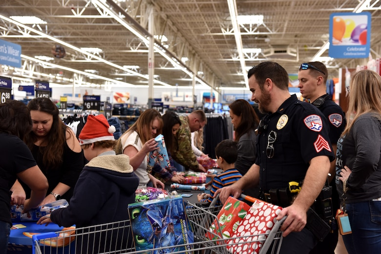 Volunteers wrap gifts purchased during the Operation Blue Santa Shop with a Cop event in San Angelo, Texas, Dec. 14, 2019. Refreshments were provided for the volunteers and participants at the event. (U.S. Air Force photo by Senior Airman Seraiah Wolf)