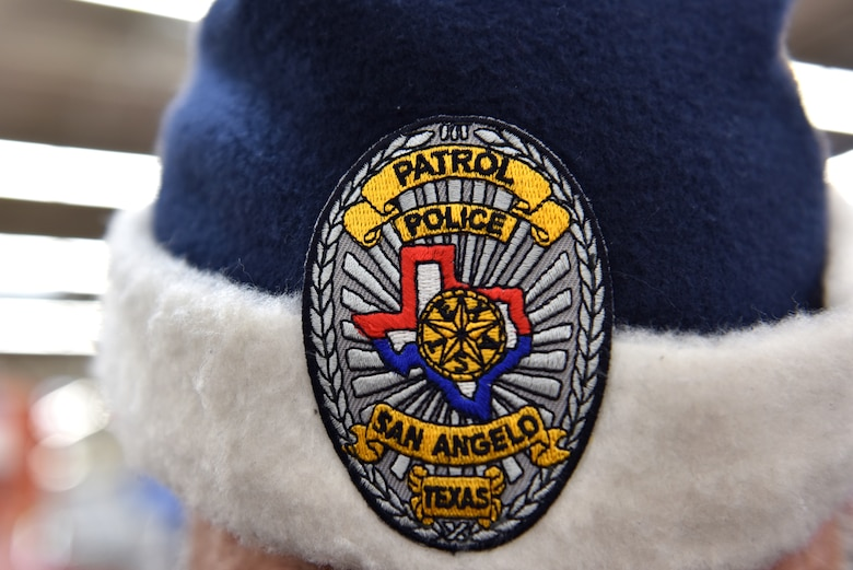 A police officer participating in Operation Blue Santa Shop with a Cop shows off his blue santa hat complete with a police badge in San Angelo, Texas, Dec. 14, 2019. This year there were multiple groups of children who shopped for their families with the police officers. (U.S. Air Force photo by Senior Airman Seraiah Wolf)