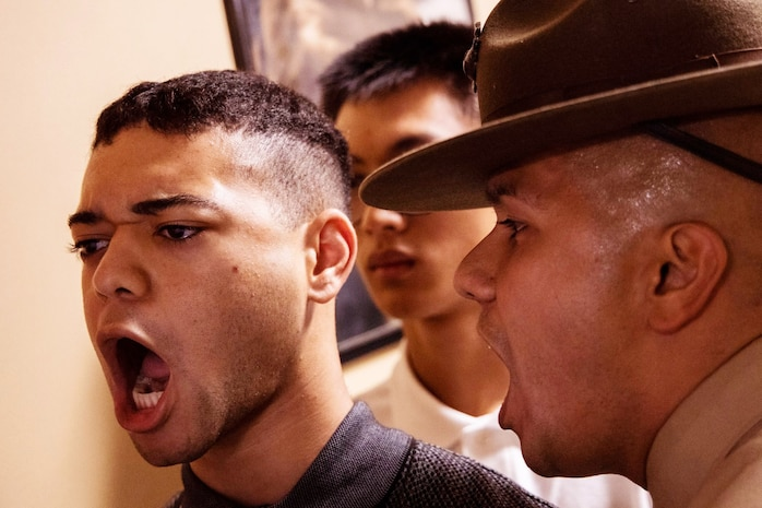 Staff Sgt. Felix Gomez, a drill instructor with Receiving Company, Support Battalion, corrects a recruit with Echo Company, 2nd Recruit Training Battalion, during receiving at Marine Corps Recruit Depot, San Diego, Dec. 9, 2019.