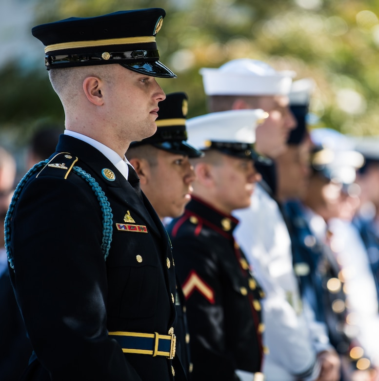 An Army soldier in dress uniform stands at attention with other service members, who are blurred into the background. A tree is also in the background.