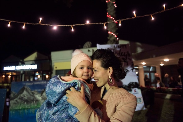 U.S. Air Force Maj. Crystal Karahan, 39th Air Base Wing executive officer, holds her daughter after the base Christmas tree lighting ceremony Dec. 5, 2019, at Incirlik Air Base, Turkey. U.S., Turkish and Spanish members of the community attended the ceremony. (U.S. Air Force photo by Staff Sgt. Joshua Magbanua)