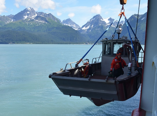 Petty Officer 3rd Class Danielle Ray from the Coast Guard Cutter Healy is lowered into Resurrection Bay near Seward, Alaska, July 21, 2017. Small boats aboard Healy are used as platforms for missions that include dive operations, scientific research and ice operations. U.S. Coast Guard photo by Senior Chief Petty Officer Rachel Polish