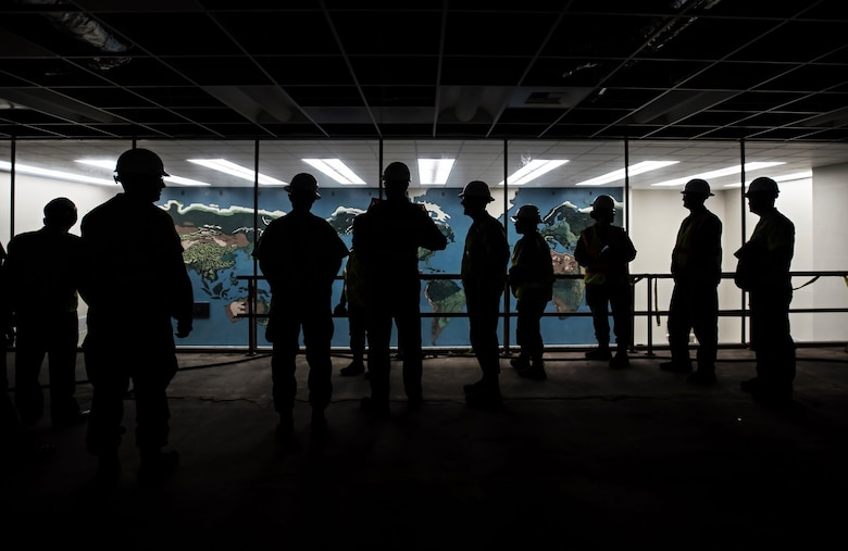 A group of military personnel in hard hats are silhouetted against the brightly lit room in front of them with a map of the world on the wall