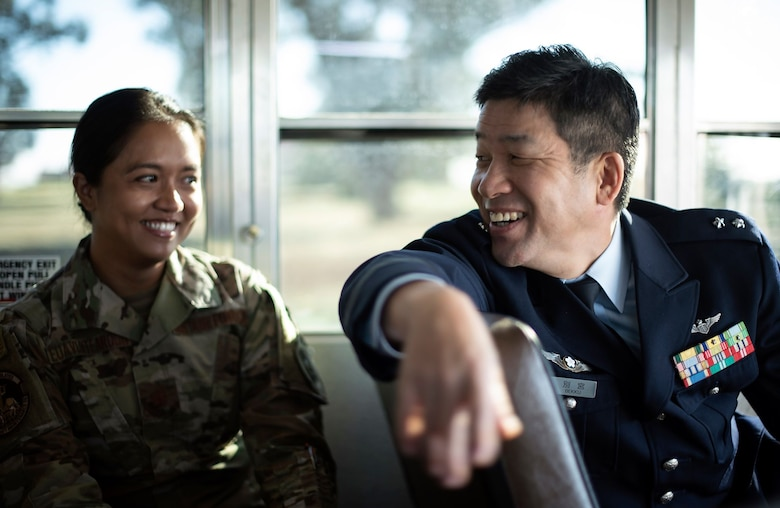 Gen. Shinya Bekku, the Japanese Surgeon General, sits on a bus and laughs with a Travis Airman in a combat uniform.