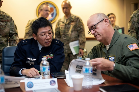 Gen. Shinya Bekku and Gen. Robert Marks pore over a pamphlet of documents. Various other military members look on.