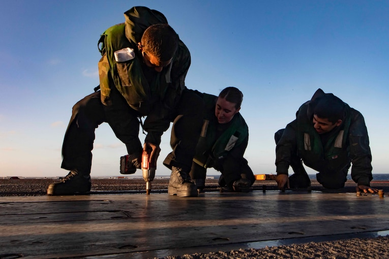 Sailors use a drill to loosen bolts on a ship's deck.