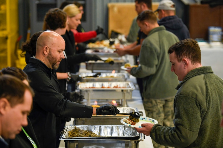 Volunteers serve food during the Feed the Troops (FTT) event at Dover Air Force Base, Del., Dec. 17, 2019. Volunteers from the local community prepared 45 turkeys and other fixings to feed more than 1,000 Airmen and family members. (U.S. Air Force photo by Senior Airman Eric M. Fisher)