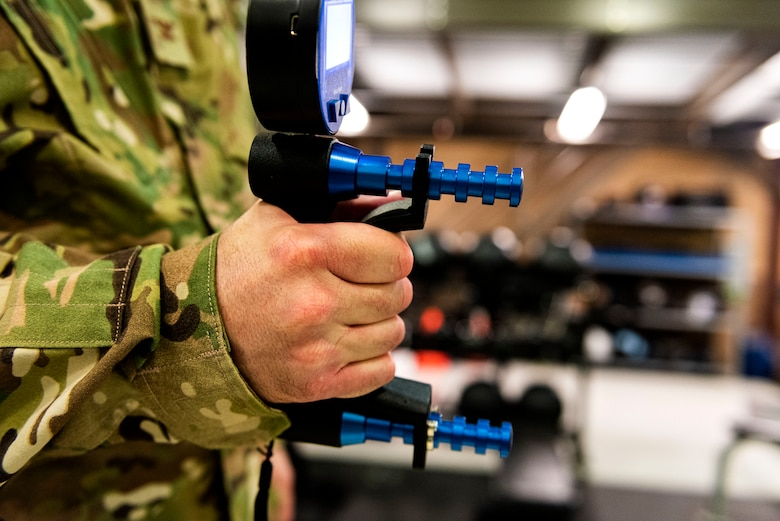A photo of Col. Dan Walls practices using a handgrip dynamometer.