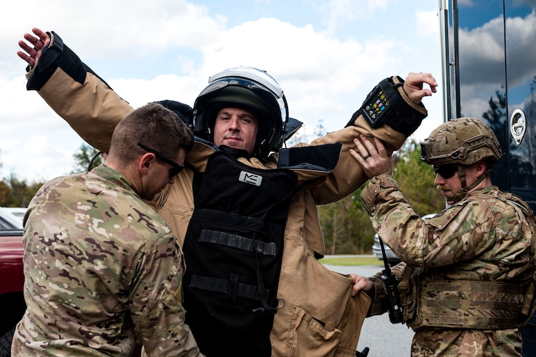 A photo of Airmen assigned to the 23d CES EOD flight putting on an EOD 9 bomb suit on Col. Dan Walls.