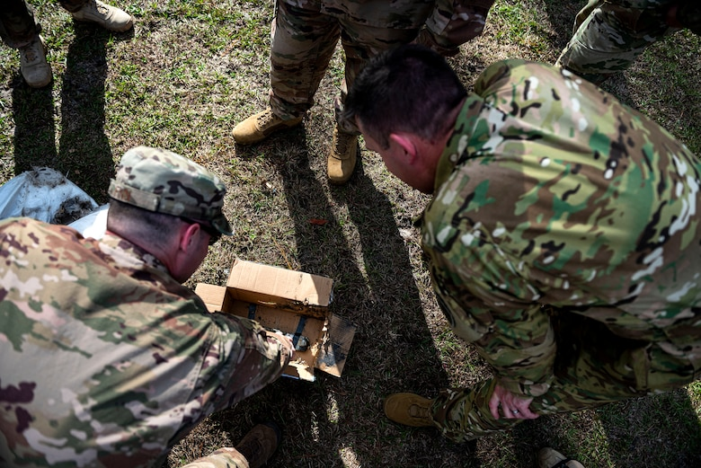 A photo of 23d Wing leadership verifying the remains of a training IED.