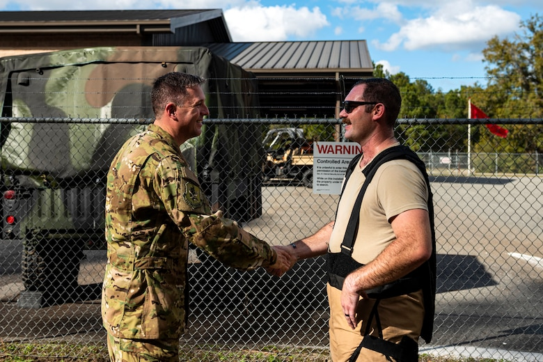 A photo of Col. Dan Walls coining an Airman assigned to the 23d CES.