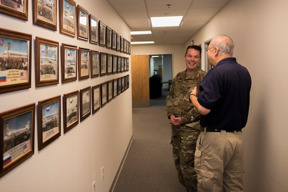 Sal Pampinella, right, International Treaty Compliance Office staff member, shares a laugh with Col. Jeffrey Nelson, left, 60th Air Mobility Wing commander, Dec. 13, 2019, at Travis Air Force Base, California. Pampinella manages and directs all activities that involve foreign visitors. Nelson toured the International Treaty Compliance Office as part of the Leadership Rounds, a program that allows base leadership to connect with personnel and gain a more in-depth understanding of each section on base. (U.S. Air Force photo by Airman 1st Class Cameron Otte)