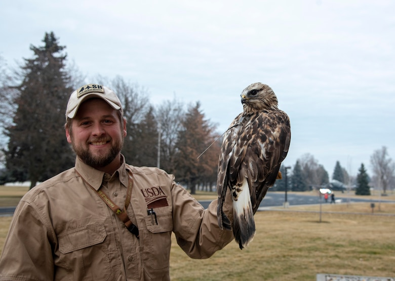 Carl Frey, United States Department of Agriculture wildlife biologist, poses for a photo with a captured rough-legged hawk at Fairchild Air Force Base, Washington, Dec. 6, 2019.