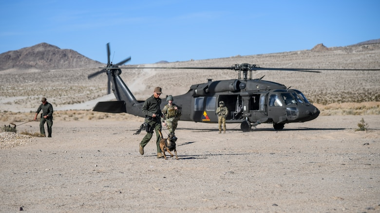 Military Working Dogs and their handlers disembark from a UH-60 Blackhawk helicopter flown by A Company, 2916th Aviation Battalion, during a joint Military Working Dog training session at the National Training Center on Fort Irwin, California, Dec. 11. (Air Force photo by Giancarlo Casem)