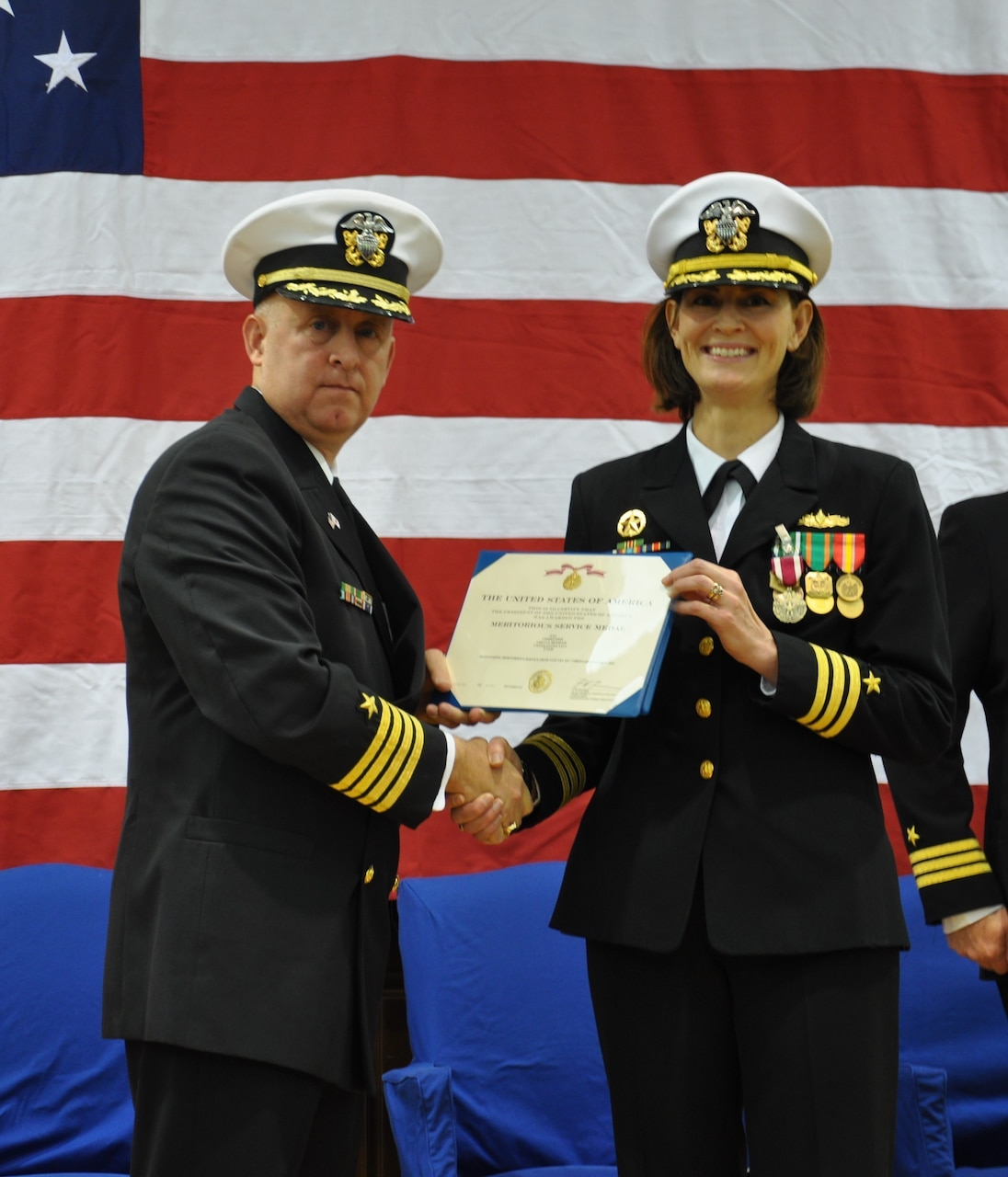 SASEBO, Japan (Dec. 12, 2019) Capt. Ed Thompson, deputy commander of Expeditionary Strike Group (ESG) 7, presents the Meritorious Service Medal to Cmdr. Greta Densham during the change of command ceremony for Naval Beach Unit (NBU) 7 onboard Commander, Fleet Activities Sasebo. Cmdr. Kirk Sowers relieved Densham as commanding officer. Under Densham's leadership, the NBU 7 team completed eight forward-deployed naval forces (FDNF) deployments, 20 multi-lateral exercises, and two disaster relief efforts in the U.S. 7th Fleet area of responsibility. In November, the unit participated in Tiger Triumph, the first-ever tri-service exercise involving the U.S. Navy and Marine Corps and Indian Army, Navy and Air Force. NBU 7, part of Expeditionary Strike Group (ESG) 7, is operating in the Indo-Pacific region to enhance interoperability with partners and serve as a ready-response force for any type of contingency.