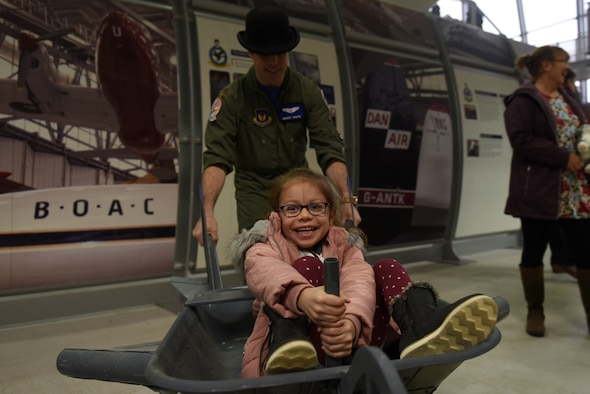 A child rides in an aircraft simulation device at the Duxford Children's Christmas Party at the Imperial War Museum, Cambridgeshire, England, Dec. 14, 2019. The event featured games, Morse code lessons, pilot displays, and a visit from Father Christmas himself. (U.S. Air Force photo by Airman 1st Class Rhonda Smith)