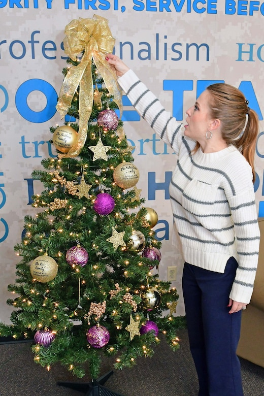 Picture shows A&FRC employee fixing the ribbon on the Gold Star Family Tree.