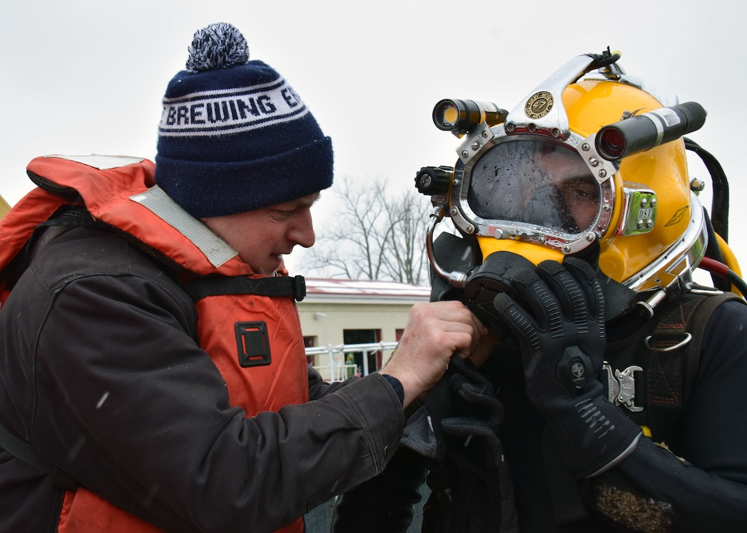 A diver receives  help attaching his dive helmet before entering the Black Rock Lock