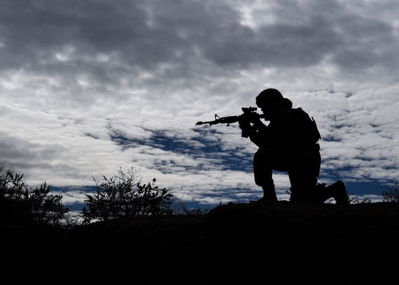 A security forces member aims his weapon at opposing forces during training.